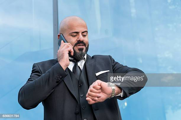bald businessman with black beard talking at smartphone