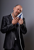 Bald crazy comic business man holding the home comfort iron and caressing it with love and closed enjoying eyes in suit on grey background. Closeup. Perfec husband loving the home domestic work