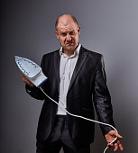 Bald fun gloomy aggressive comic business man holding the home iron and wanting to hit in suit on grey background. Closeup portrait