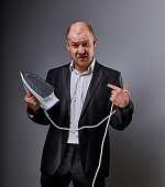 Bald fun gloomy comic business man holding the home iron and not want to ironing on grey background. Closeup portrait