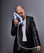 Bald fun tired unhappy loser failed business man punishing himself holding the home iron near the face in suit on grey background. Closeup portrait