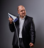 Bald fun unhappy aggressive comic business man holding the home iron and wanting to hit in suit on grey background. Closeup