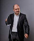 Bald fun unhappy aggressive comic business man holding the home iron and wanting to hit in suit on grey background. Closeup portrait