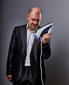 Bald fun unhappy menacing aggressive business man holding the home iron and wanting to hit in suit on grey background. Closeup portrait