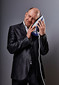 Bald happy comic business man holding the home comfort iron and caressing it with love and closed enjoying eyes in suit on grey background. Closeup. Perfec husband loving the home domestic work