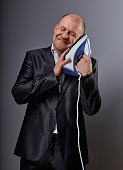 Bald happy comic business man holding the home iron near the face with love and closed enjoying eyes in suit on grey background. Closeup. Perfec husband loving the home domestic work