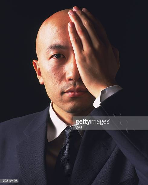 A bald headed businessman covering an eye with hand, Front View