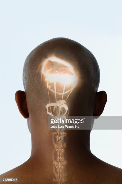 Bald Hispanic man with light running up spine