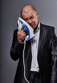 Bald loser suffering business man holding the home iron near the face with sad face in suit on grey background. Closeup portrait