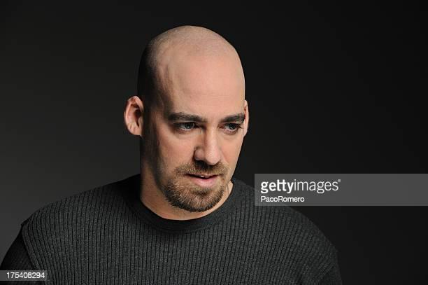Bald man against black background