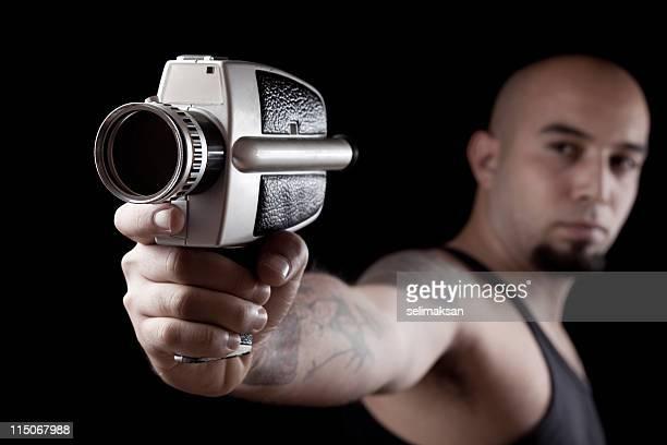 Bald man holding and aiming camera as gun