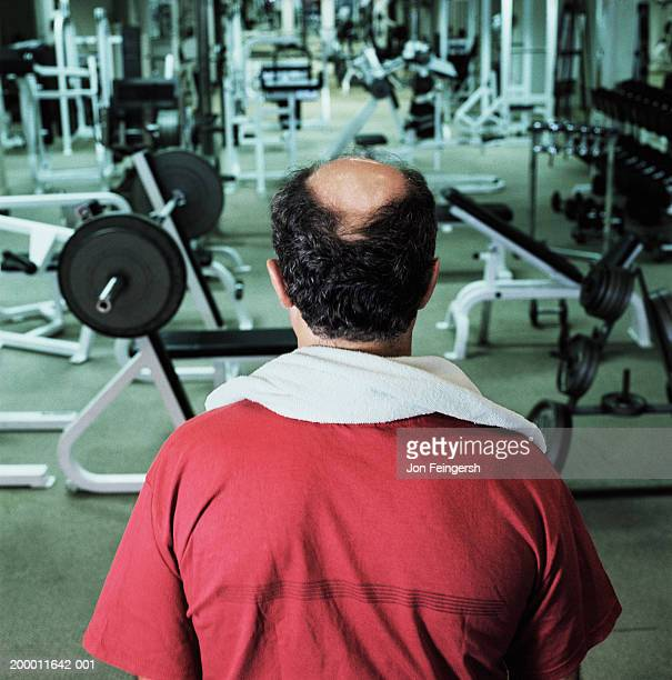 Bald man in gym looking at exercise equiptment, rear view