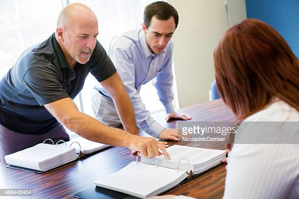 Bald man points to small print during meeting