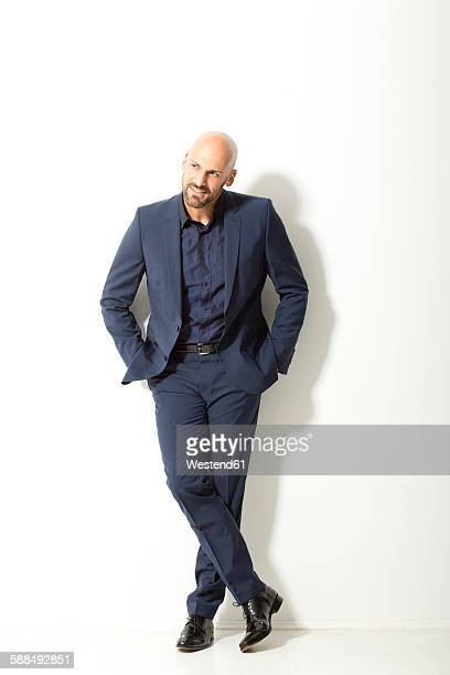 Bald man with beard wearing blue suit standing in front of white background