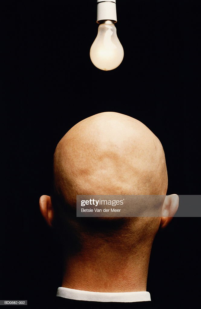Bald man with illuminated lightbulb above head, rear view