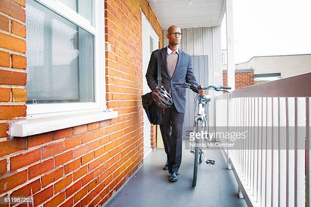 Bald mature African man leaving home with bicycle