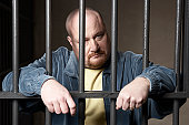 Bald mid-adult man standing behind prison bars