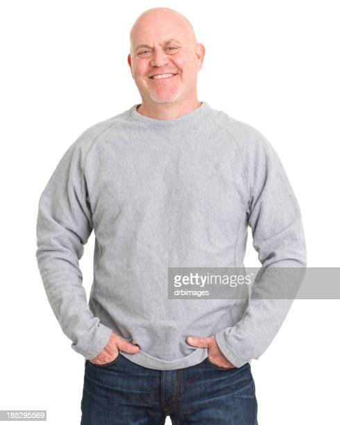 Bald middle aged man posing with his hands in his pockets