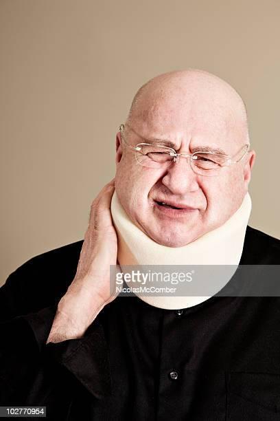 Bald senior man hurting from neck injury