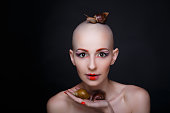 Beautiful bald woman keeps large slimy snails. Perfect beige skin sexual naked shoulders. Sexy passionate girl with informal strange appearance conceptual. Black background free place Closeup portrait