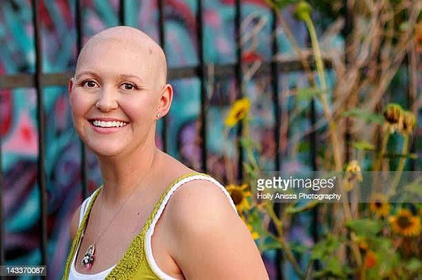Bald woman with cancer in front of graffiti wall