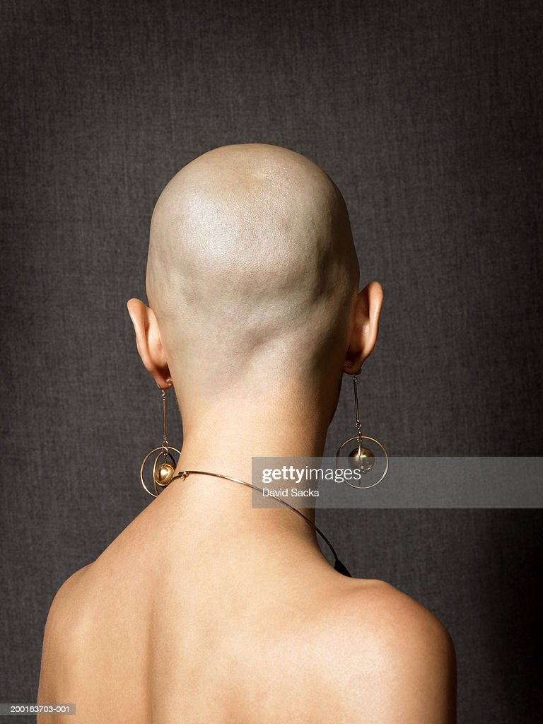 Bald woman with dangling earrings, close-up, rear view : Stock Photo