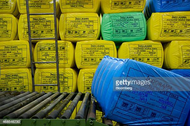 A bale of polyester staple fibre moves along a conveyor past other bales of polyester staple fibre in a storage area at the Indorama Polyester...