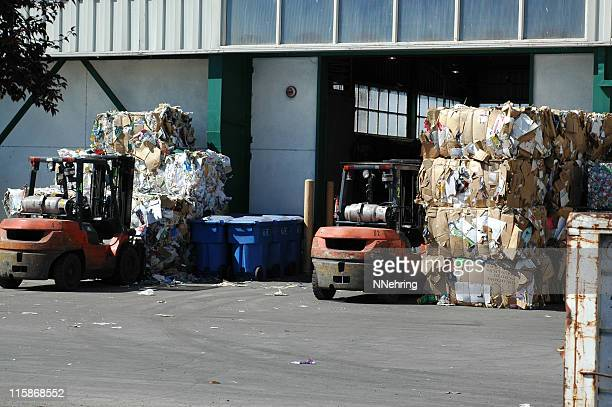 bales of cardboard and forklifts at recycling center