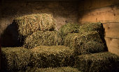 Bales of hay in a stone and wood barn
