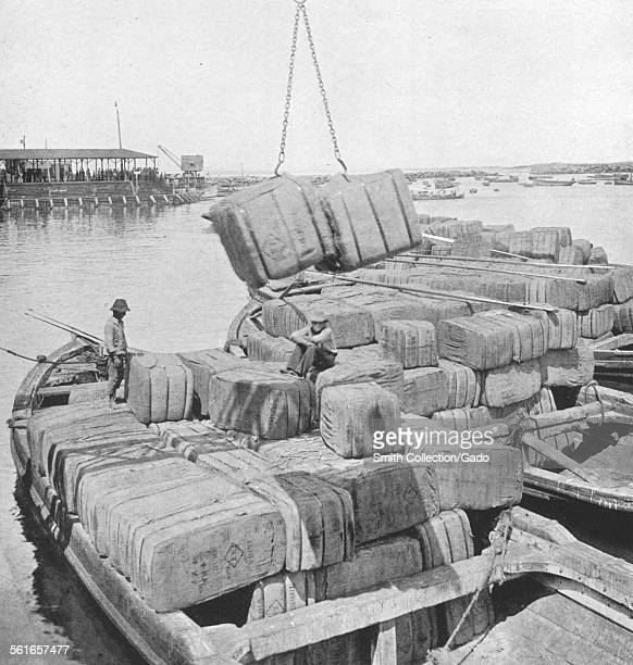 Bales of jute bags from India for the nitrate fields on a ship in a harbor being loaded by two men with a crane 1922