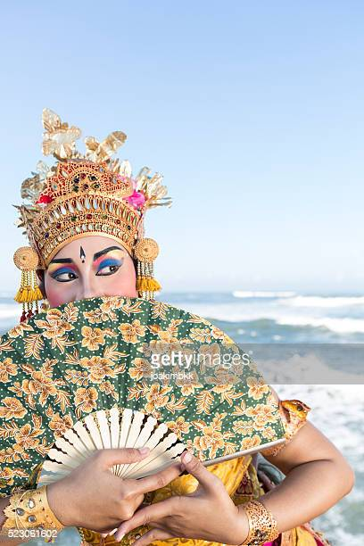 Bali female dancer in traditional costume with fan on beach