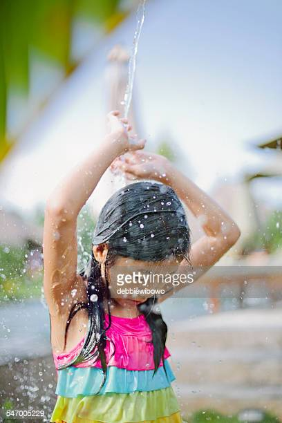 Bali, Girl (8-9) playing with water
