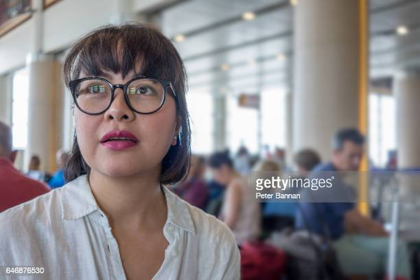 Bali, Indonesia, Asian woman at airport departures, looking up at flight information