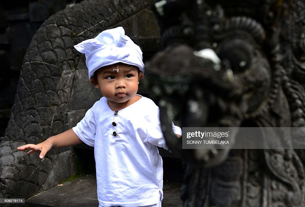 A Balinese boy wears a traditional outfit at a temple to celebrate Galungan day in Jimbaran, on Indonesia's resort island of Bali on February 10, 2016. Galungan Day is a holiday celebrated by Balinese as a sign of victory of good against evil. AFP PHOTO/SONNY TUMBELAKA / AFP / SONNY TUMBELAKA