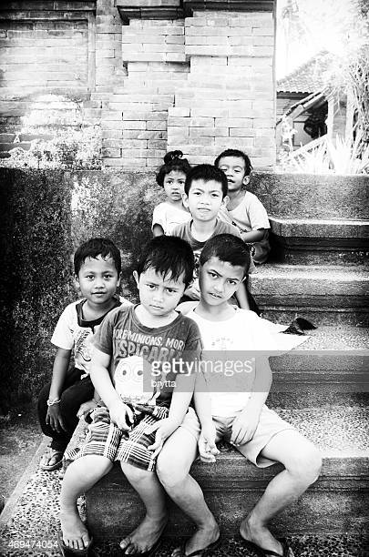 Balinese children sitting on stairs in front of family compound