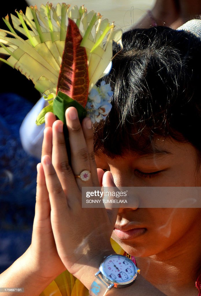 A Balinese girl prays during the Hindu Saraswati holy day at a school in Denpasar on Bali island on August 10, 2013. Hindu devotees in Bali celebrated Saraswati day - the day to worship God in his manifestation as the master of all knowledge.