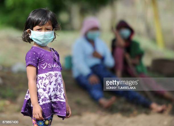 A Balinese girl wears a mask as she looks at her mother planting as Mount Agung erupts in Kubu subdistrict in Karangasem Regency on Indonesia's...