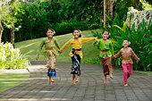 Balinese girls laughing and running