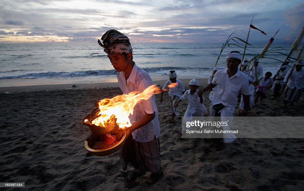 A Balinese Hindu devotee carries oil lamp during Melasti Ritual ceremony on March 9, 2013 in Denpasar, Bali, Indonesia. The Melasti Ritual is held annually ahead of the Nyepi Day of Silence a ceremony intended to cleanse and purify the souls of the Balinese Hindu participants. Nyepi is a Hindu celebration observed every new year according to the Balinese calendar. The national holiday is one of elf-reflection and meditation and activities such as working, watching television or travelling are restricted between the hours of 6am and 6pm.