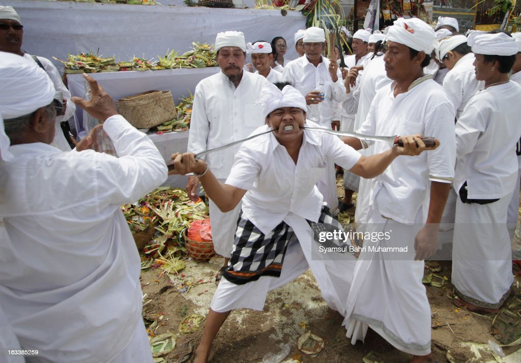 A Balinese Hindu devotee in a trance stabs himself with traditional daggers called 'keris' during a Melasti Ritual ceremony on March 9, 2013 in Denpasar, Bali, Indonesia. The Melasti Ritual is held annually ahead of the Nyepi Day of Silence a ceremony intended to cleanse and purify the souls of the Balinese Hindu participants. Nyepi is a Hindu celebration observed every new year according to the Balinese calendar. The national holiday is one of elf-reflection and meditation and activities such as working, watching television or travelling are restricted between the hours of 6am and 6pm.