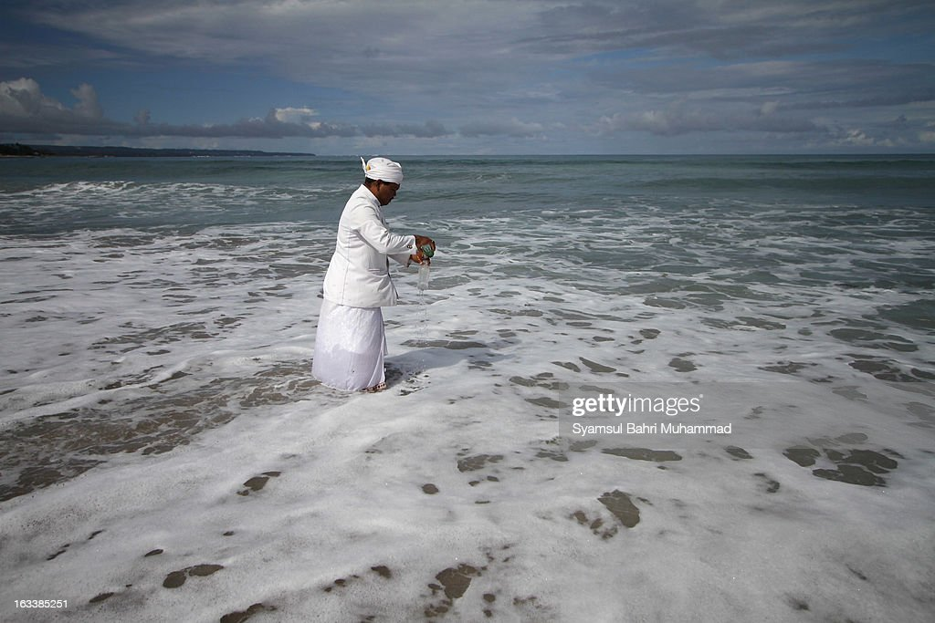 A Balinese Hindu devotee prepares offerings during Melasti Ritual ceremony on March 9, 2013 in Denpasar, Bali, Indonesia. The Melasti Ritual is held annually ahead of the Nyepi Day of Silence a ceremony intended to cleanse and purify the souls of the Balinese Hindu participants. Nyepi is a Hindu celebration observed every new year according to the Balinese calendar. The national holiday is one of elf-reflection and meditation and activities such as working, watching television or travelling are restricted between the hours of 6am and 6pm.