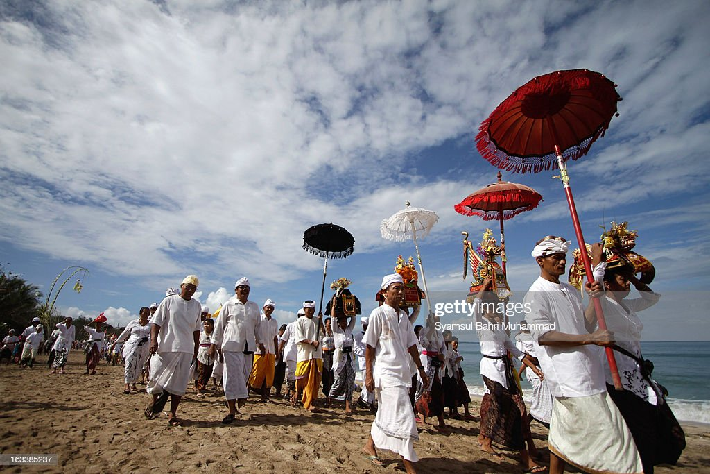 Balinese Hindu devotees carry offerings during Melasti Ritual ceremony on March 9, 2013 in Denpasar, Bali, Indonesia. The Melasti Ritual is held annually ahead of the Nyepi Day of Silence a ceremony intended to cleanse and purify the souls of the Balinese Hindu participants. Nyepi is a Hindu celebration observed every new year according to the Balinese calendar. The national holiday is one of elf-reflection and meditation and activities such as working, watching television or travelling are restricted between the hours of 6am and 6pm.