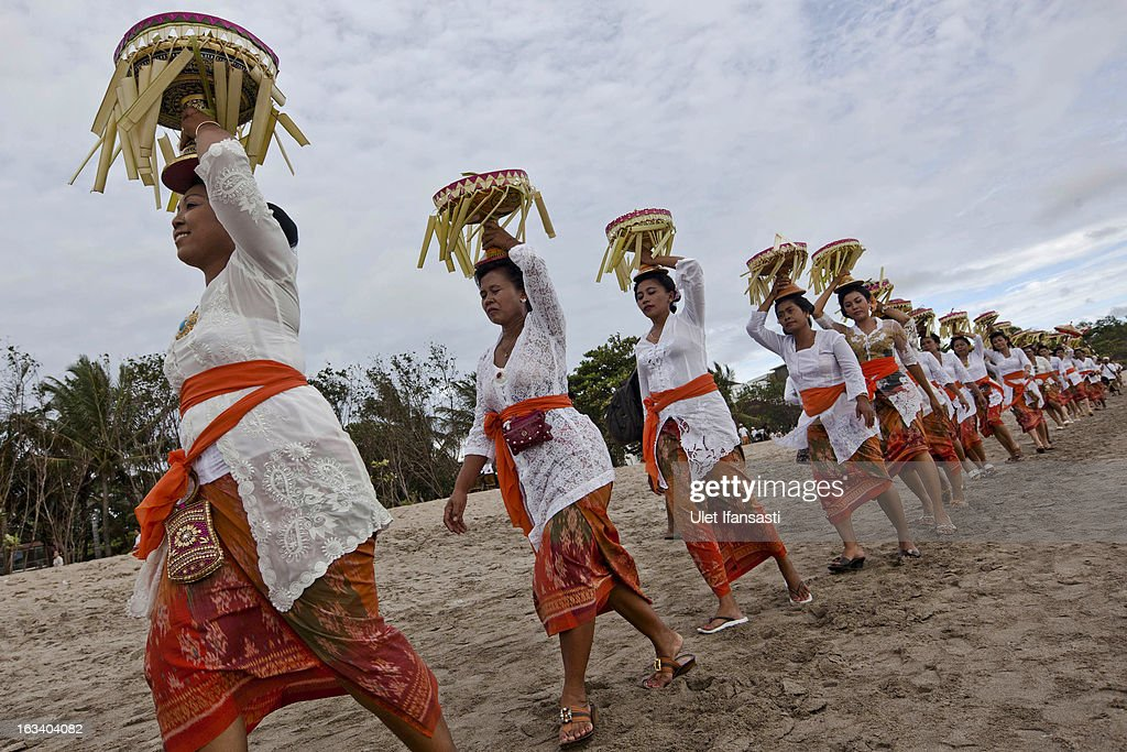 Balinese Hindu devotees carry offerings during the Melasti ritual on March 9, 2013 in Denpasar, Bali, Indonesia. The Melasti ritual is held annually ahead of the Nyepi Day of Silence, a ceremony intended to cleanse and purify the souls of the Balinese Hindu participants. Nyepi is a Hindu celebration observed every new year according to the Balinese calendar. The national holiday is one of self-reflection and meditation and activities such as working, watching television or travelling are restricted between the hours of 6 a.m. and 6 p.m.