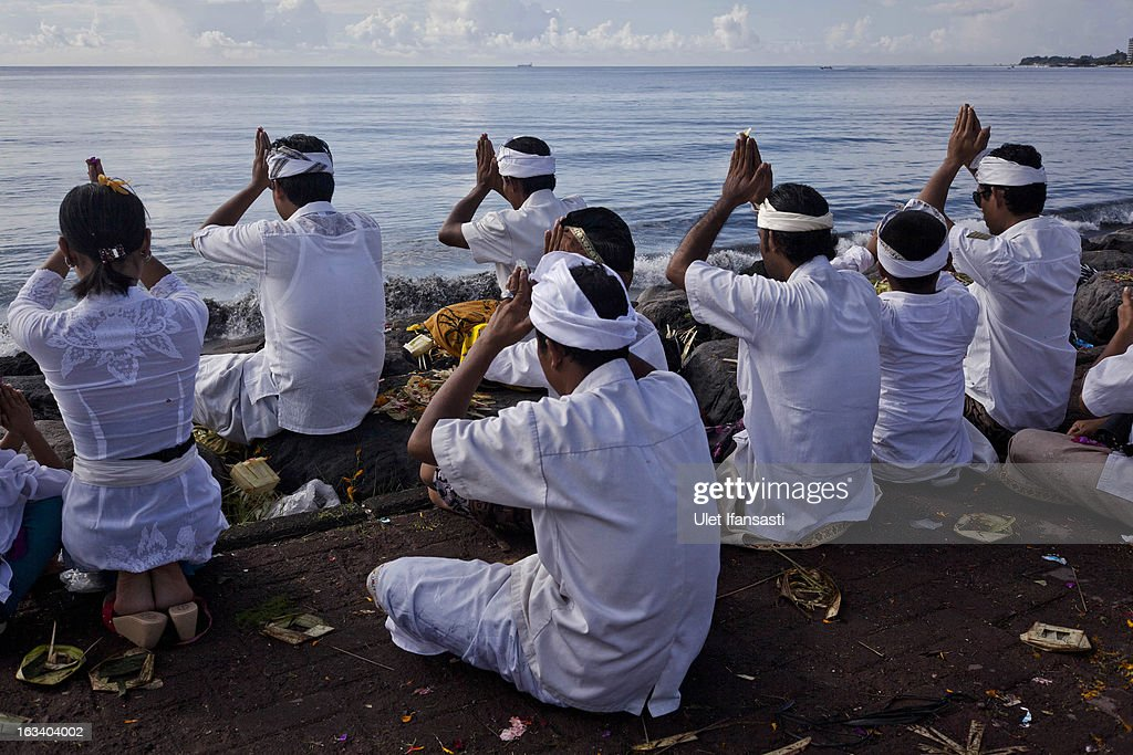 Balinese Hindu devotees pray during the Melasti ritual on March 9, 2013 in Denpasar, Bali, Indonesia. The Melasti ritual is held annually ahead of the Nyepi Day of Silence, a ceremony intended to cleanse and purify the souls of the Balinese Hindu participants. Nyepi is a Hindu celebration observed every new year according to the Balinese calendar. The national holiday is one of self-reflection and meditation and activities such as working, watching television or travelling are restricted between the hours of 6 a.m. and 6 p.m.