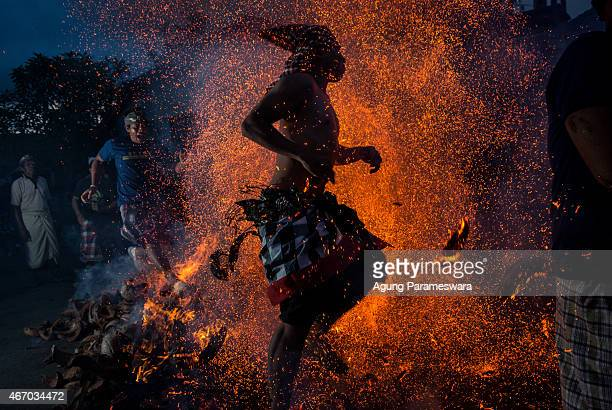 Balinese man kicks up the fire during the 'Mesabatan Api' ritual ahead of Nyepi Day on March 20 2015 in Gianyar Bali Indonesia Mesabatan Api is held...