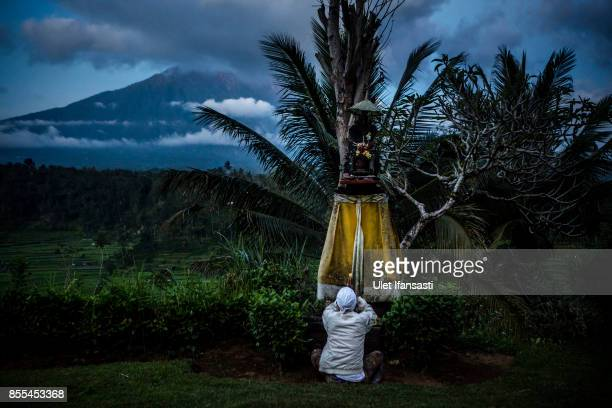 KARANGASEM BALI INDONESIA SEPTEMBER 29 A balinese man prays with mount Agung in the backround on September 29 2017 in Karangasem regency Island of...