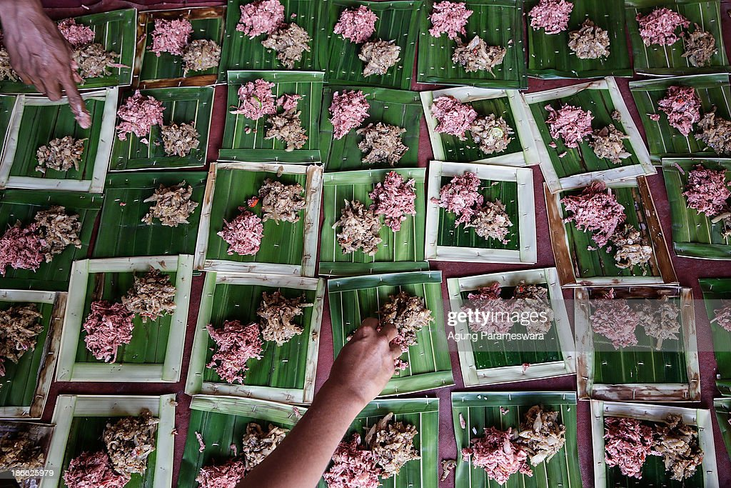 Balinese man puts 'lawar' (chopped meat and vegetables mixed) as he prepare to megibung, a collective feast, in front of the gates of Panti temple during Dewa Masraman ritual on November 2, 2013 at Paksabali Village in Klungkung Regency, Bali, Indonesia. The Dewa Masraman ritual pays homage to gods through offerings and various activities centered around the gods throughout the day. The morning is spent eating traditional food, parading the deities effigies which are installed in palanquins and making offerings. In the afternoon a battle is held in which dozens of men carry the palanquins rushing around the temple in a trance like state, crashing into each other.
