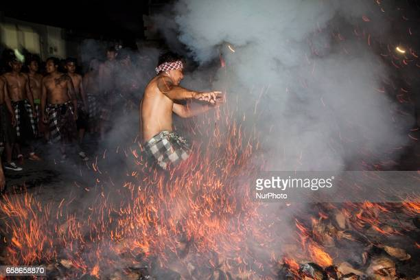 A Balinese man runs through flames as part of the mesabatan api or battle of the fire in Bali Indonesia on March 27 a ritual held on the eve of Nyepi...