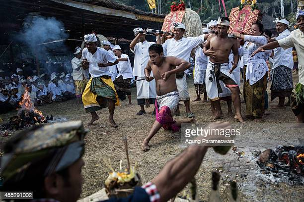 KARANGASEM BALI INDONESIA SEPTEMBER 11 Balinese men dance in a state of trance while carrying palanquins the symbol of god during a sacred ritual of...