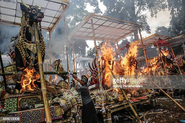 Balinese men throw offerings to a sarcophagus in the shape of buffalo during Balinese Hindu mass cremation on August 1 2014 in Ubud Bali Indonesia...